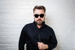 Portrait of a bearded serious man in sunglasses, a black shirt and tie against a white brick wall. The man is pulling himself by the tie