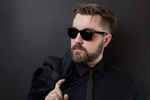 A brutal man with a beard and a stylish hairstyle in a black shirt and tie is holding his jacket. Young business man after a hard day at work on a black background