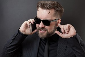 A businessman in a black suit and glasses is talking on the phone. He does not hear his interlocutor, so he plugs his free ear with his finger. Problem with cellular communication