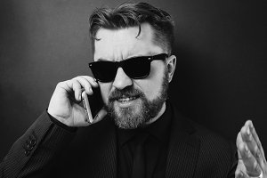 A businessman in a black suit swears by phone with his subordinates. A man in sunglasses speaks on the phone, gesturing with his hands against a black background