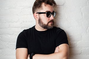 Portrait of a bearded serious man in sunglasses and casual clothes against a white brick wall