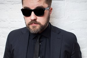 Portrait of a bearded serious man in sunglasses and a business black suit against a white brick wall