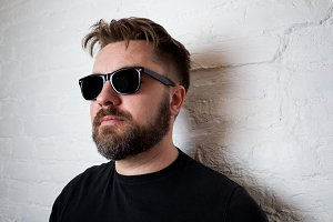 Portrait of a bearded serious man in sunglasses and casual clothes against a white brick wall.