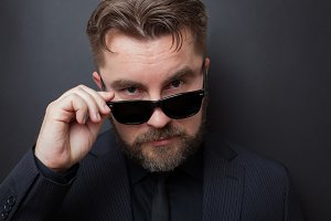A brutal man with a beard and a stylish hairstyle in a black suit looks appallingly at the camera, dropping his sunglasses