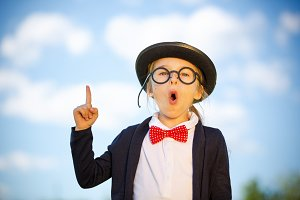 Funny little girl in glasses, bow tie and bowler hat.