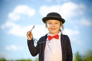 Funny little girl in bow tie and bowler hat.