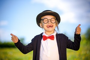 Funny little girl in bow tie and bowler hat showing thumbs up.