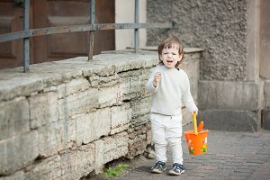 Little boy with long blond hair crying standing on the street. In his hand he is holding an orange bucket to play in the sandbox