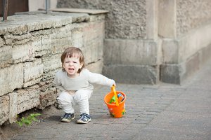 Little boy with long blond hair crying standing on the street. In his hand he is holding an orange bucket to play in the sandbox. Stomach hurts