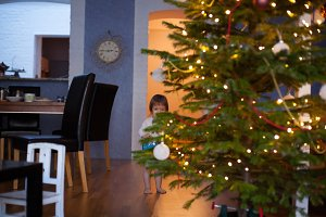 Funny little child is hiding behind the Christmas tree