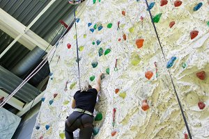 Young athletic woman practicing rock-climbing on a rock wall indoors
