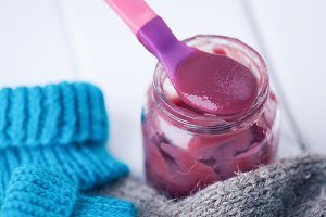 Jar baby fruit puree on wooden background
