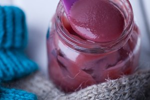 Jar baby fruit puree on wooden background