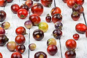 Different tomatoes on the wooden background