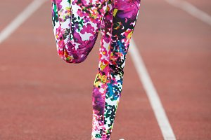 Legs sports girl in bright tights and grey sneakers on the Jogging path. Woman warming up before a run