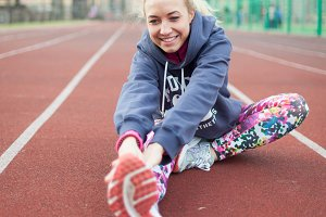 Young beautiful blonde hair fitness girl doing stretching on the stadium. Summer sport activity