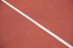 Diagonal white line marking red stadium with soft coverings for sports