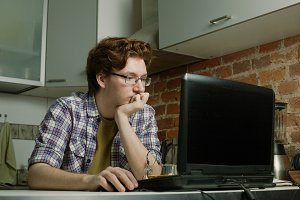 Young man sitting at a laptop and thinks about problem solving
