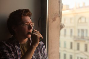 Young man smoking electronic cigarette near window.