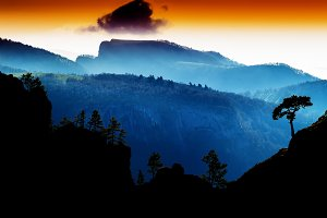 Horizontal vdramatic mountain trees on rocks silhouette sunset b