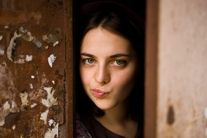 A young curious girl looks out from behind the door of her house. She thinks about going outside. agoraphobia concept