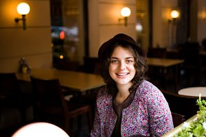 Beautiful young woman in a hat with a cup of tea sitting in a cafe looking at the camera and smiling