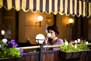 Beautiful young woman in a hat sits on a terrace in a cafe, drinks tea and looks at the camera
