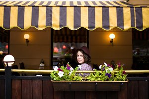 Beautiful young woman in a hat sits on a terrace in a cafe and looks at the camera