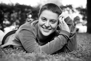 Portrait of a beautiful girl with short hair and green eyes lies on the grass, smiling and looking at the camera