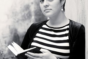 A girl with big eyes and short hair reads a book, standing by the wall. Preparing for exams at the university. Close-up portrait. Black and white photo