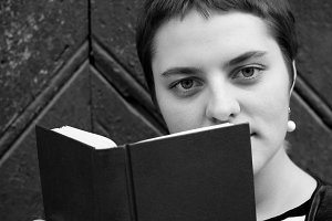 A girl with big eyes and short hair hides behind a book. Close-up portrait. Black and white photo