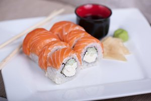 Philadelphia sushi roll with red fish on a white plate