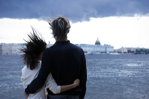 Back view of man and woman huging together on the bridge