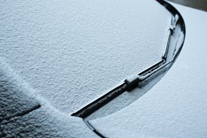 Snow-covered windshield wipers and windshield on the car