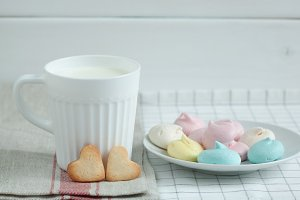 Cookies in the form of hearts and meringue milk.