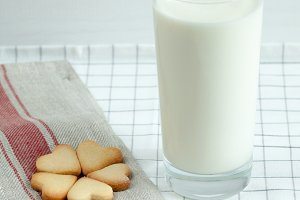 Cookies in the form of hearts with milk.