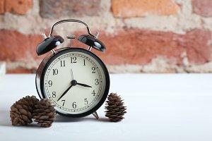 Retro alarm clock on the brick wall background.
