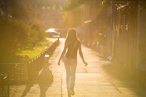 She walks around the city. Backlight. Summer mood.