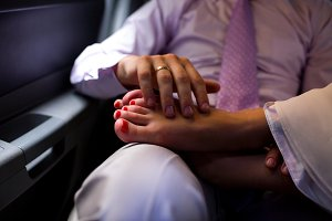 The groom pats the tired feet of his bride in the limo. Wedding moments