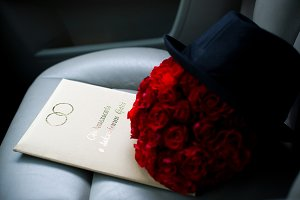 Bridal bouquet of roses next to the hat of the groom