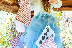 An little beautiful girl playing and dancing with large playing cards on the table