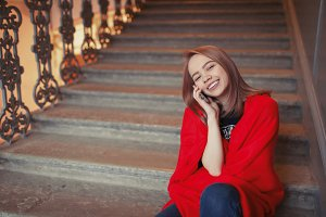 A young blonde girl talking on the phone sitting on the steps, wrapped in a red blanket. She is happy and smiling