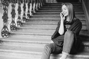 A young blonde girl talking on the phone sitting on the steps.She is happy and smiling