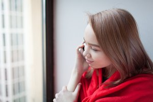 Young blonde girl talking on the phone sitting by the window, wrapped in a red blanket