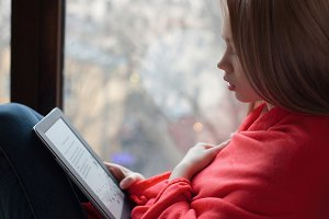 Portrait of a young girl reading an e-book at the window