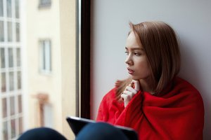 A young girl sits by the window with an e-book, wrapped in a red blanket and thinks