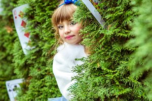 An little beautiful girl in a long blue dress looking from under the fir trees