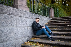 A young guy sitting on the stairs in the Park among the yellow leaves