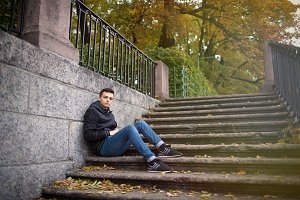 A young guy sitting on the stairs in the Park among the yellow l