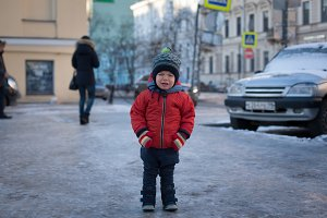 Little boy in a red jacket crying in the street.